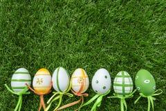 Une rangée de cinq oeufs de pâques colorés sur l'herbe verte Images stock