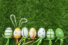 Une rangée de cinq oeufs de pâques colorés sur l'herbe verte avec le lapin ea Image libre de droits