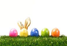 Une rangée de cinq oeufs de pâques colorés sur l'herbe verte avec le lapin ea Photographie stock libre de droits