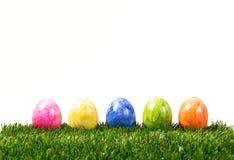 Une rangée de cinq oeufs de pâques colorés sur l'herbe verte d'isolement sur le wh Photographie stock libre de droits