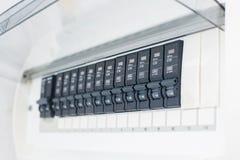 Une rangée de commuter outre des disjoncteurs électriques de ménage sur un panneau de mur Image libre de droits