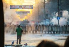 Une rangée de la police anti-émeute avec un prêtre à la rue de Hrushevskogo dedans Image stock