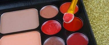 Une rangée de maquillage ou de cosmétiques dispersés au-dessus d'un fond de scintillement d'or Un applicateur d'éponge est chargé image libre de droits