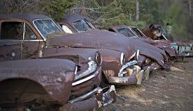 Une rangée des automobiles abandonnées rouillées rassemblées Image stock