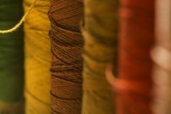 Une rangée des bobines de fil de couture de différentes couleurs Image libre de droits