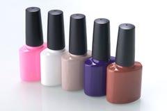 Une rangée des bouteilles multicolores avec le vernis à ongles sur une table blanche images libres de droits