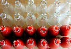 Une rangée des bouteilles a rempli de sauce tomate à côté des bouteilles vides images stock