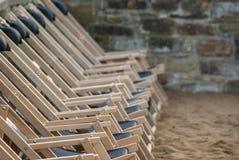Une rangée des chaises de plate-forme vides suspendues dans les rangées a aligné dans l'ordre sur la plage dans le sable Photos libres de droits