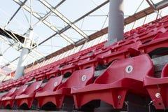 Une rangée des chaises en plastique rouges sur un stade Photos stock