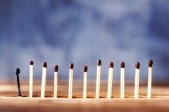 Une rangée des matchs sur un fond en bois, le dernier match a brûlé d images libres de droits