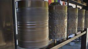 Une rangée des roues de prière bouddhistes, l'une d'entre elles tourne images libres de droits