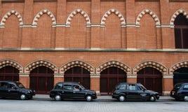 Une rangée des taxis noirs de Londres image libre de droits