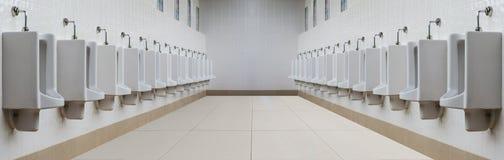 Une rangée des urinoirs dans le mur carrelé dans des toilettes publiques Images stock