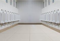 Une rangée des urinoirs dans le mur carrelé dans des toilettes publiques Photos libres de droits