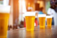 Une rangée des verres de bière en plastique avec de la bière blonde Images stock