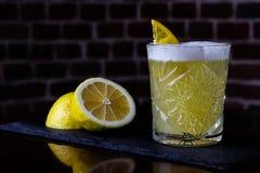 Une recette classique pour aigre de whiskey - le bourbon, le sirop de canne et le jus de citron, étant garni avec l'orange Apérit photos stock