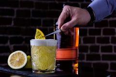 Une recette classique pour aigre de whiskey - le bourbon, le sirop de canne et le jus de citron, étant garni avec l'orange Apérit photographie stock libre de droits