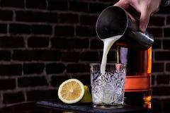 Une recette classique pour aigre de whiskey - le bourbon, le sirop de canne et le jus de citron, étant garni avec l'orange Apérit photo libre de droits