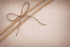 Une relation étroite de proue avec deux cordes allant diagonalement sur le fond de tissu Photo libre de droits