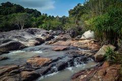 Une rivière raide entrant au-dessus de grandes pierres dans la jungle Images stock