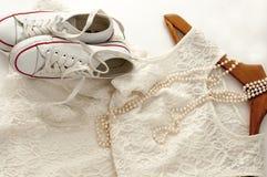 Une robe blanche de dentelle, une paire d'espadrilles sur un cintre en bois et un collier de perle sur le blanc Images stock