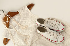 Une robe blanche de dentelle, une paire d'espadrilles sur un cintre en bois et un collier de perle sur le blanc Photographie stock