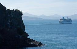 Une roche dans le premier plan, à l'arrière-plan un grand bateau de croisière laissant la péninsule d'Otago près de Dunedin au No image libre de droits