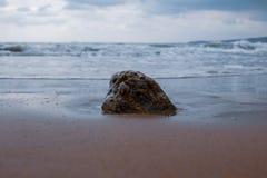 Une roche dans le sable dans le sable d'une plage grecque avec de l'eau turquoise image stock