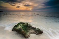 Une roche et un coucher du soleil de plage Photographie stock