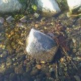 Une roche se tient parmi un courant débordant image libre de droits