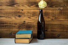 Une rose blanche dans une bouteille et livres Images stock