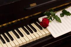 Une rose de rouge avec le papier de notes sur le piano Photo stock