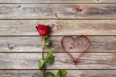 Une rose de rouge sur le fond en bois avec le coeur du ruban valentin Image libre de droits