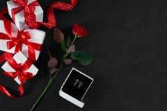 Une rose et boîte rouge foncé avec des boucles d'oreille sur le fond noir rom Image libre de droits