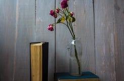 Une rose rouge dans une bouteille et livres Photos libres de droits