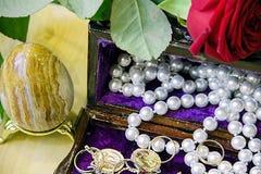 Une rose rouge se trouve sur la boîte à bijoux