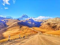 Une route à la montagne couronnée de neige images libres de droits