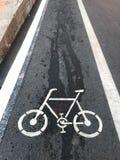Une route avec un symbole de bicyclette peint là-dessus photographie stock libre de droits