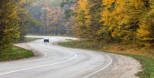 Une route d'enroulement dans les arbres forestiers d'automne avec les feuilles jaunies par la route photo libre de droits
