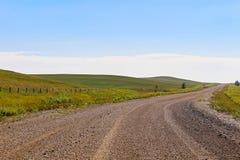 Une route de gravier par des terres cultivables et des collines d'Alberta images libres de droits