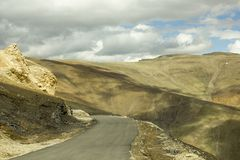 Une route de montagne avec l'ombre des nuages photographie stock libre de droits