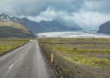 Une route de regard isolée de route courbant loin en montagnes avec des gouttes de pluie sur le verre de fenêtre, jour pluvieux,  photo stock