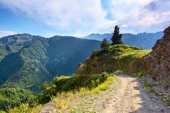 Une route large avec une falaise mène vers le bas au haut mountai de Caucase Photographie stock libre de droits