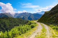 Une route large avec une falaise mène vers le bas au haut mountai de Caucase Images libres de droits