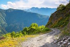 Une route large avec une falaise mène vers le bas au haut mountai de Caucase Photos stock