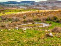 Une route serpente par des terres cultivables Photographie stock libre de droits
