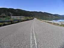 Une route vide à côté d'un lac, Photos libres de droits