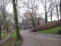 Une rue pavée en cailloutis avec le cycliste par un parc à Utrecht, Pays-Bas photographie stock