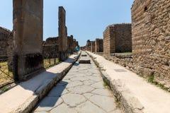 Une rue pav?e en cailloutis antique dans les ruines de Pompeii, Italie photo stock
