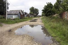 Une rue triste de pays avec des magmas et de vieilles maisons image libre de droits